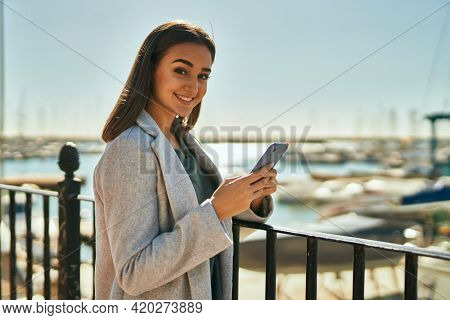 Young hispanic girl using smartphone leaning on the balustrade at the port.