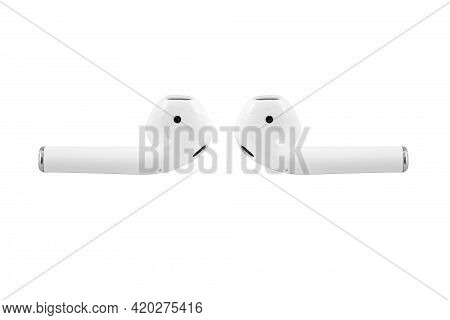 White Wireless Earbuds Headphones Lying In Front Of Each Other. White Earflaps Isolated On White Bac