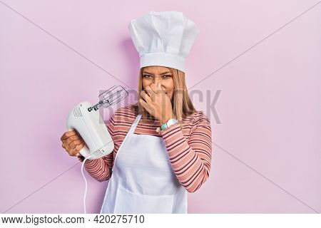 Beautiful hispanic woman holding pastry blender electric mixer smelling something stinky and disgusting, intolerable smell, holding breath with fingers on nose. bad smell