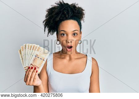 Young african american girl holding 100 danish krone banknotes scared and amazed with open mouth for surprise, disbelief face