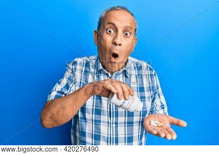 Senior hispanic man holding pills afraid and shocked with surprise and amazed expression, fear and excited face.