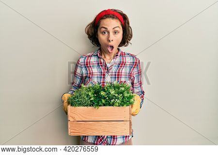 Young brunette woman wearing gardener clothes holding wooden plant pot afraid and shocked with surprise and amazed expression, fear and excited face.