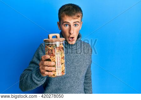 Young caucasian man holding jar of uncooked pasta scared and amazed with open mouth for surprise, disbelief face