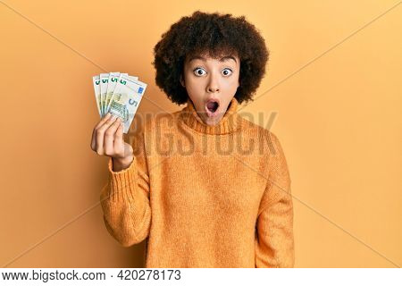 Young hispanic girl holding bunch of 5 euro banknotes scared and amazed with open mouth for surprise, disbelief face