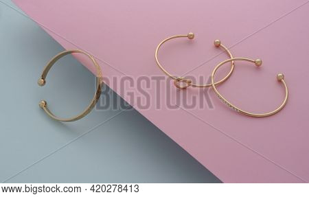 Three Modern Golden Bangles On Pink And Blue Background With Copy Space
