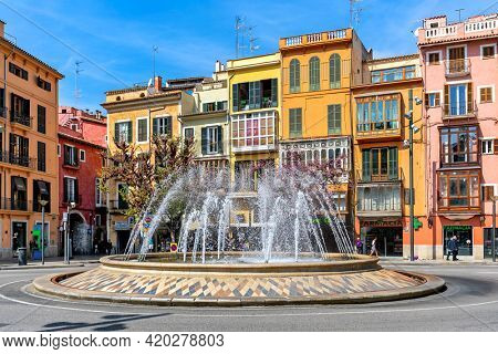 PALMA, SPAIN - APRIL 12, 2019: Fountain and colorful building on Plaza de la Reina - one of the famous and popular places located in the historical and tourist centre of Palma de Mallorca.