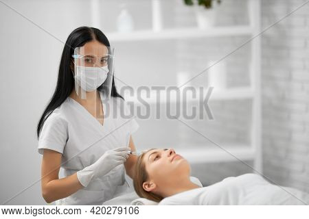 Side View Of Young Beautician In White Uniform And Protective Mask Holding Syringe And Doing Beauty