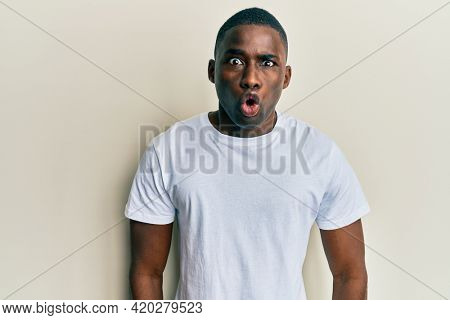 Young african american man wearing casual white t shirt scared and amazed with open mouth for surprise, disbelief face