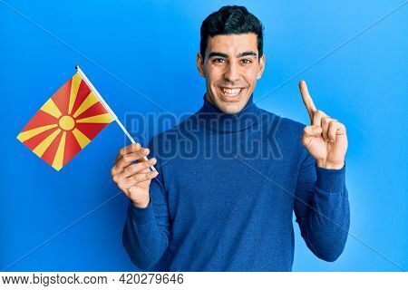Handsome hispanic man holding macedonian flag smiling with an idea or question pointing finger with happy face, number one