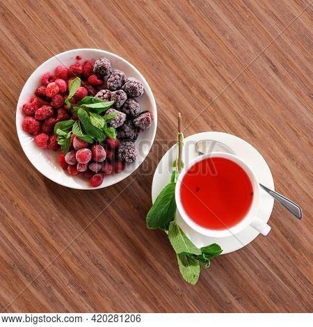 Teacup, Top View. Red Tea From Frozen Berries, Blackberries, Raspberries And Cherries With Mint Leav