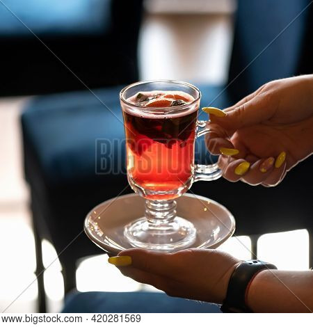 Woman Holding Cup Of Fruit Herbal Tea Backlit By Sunlight. Close-up Shot Of Female Hands With Fresh