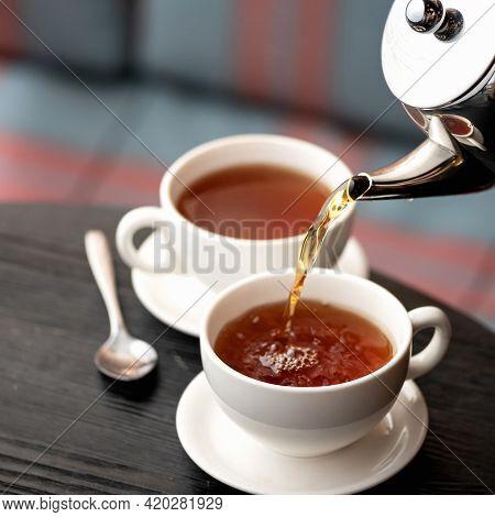 Black Tea Pouring From Metal Teapot Into Ceramic Cups. Tea Ceremony Concept. Soft Focus.