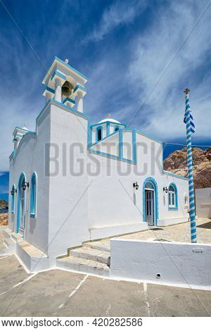 Greek village scenic picturesque view in Greece - Orthodox church in fishing village of Firapotamos in Milos island, Greece