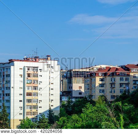 Apartment Buildings With Balconies And Blue Sky. Lush Greenery. Bright Sunshine