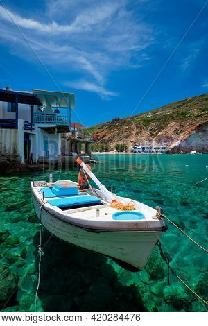 Greek village scenic picturesque view in Greece - fishing boat and fishing village of Firapotamos with beach in Milos island, Greece