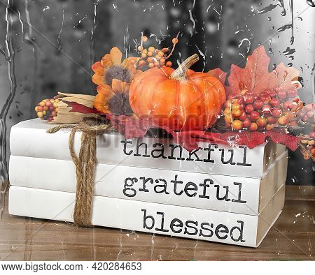 Stack Of Books With Autumn Pumpkin And Thanksgiving Text Tied With String And Raindrop Overlay