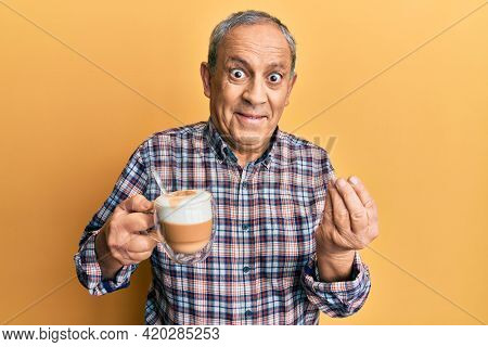 Handsome senior man with grey hair drinking a cup coffee doing money gesture with hands, asking for salary payment, millionaire business