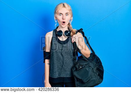 Beautiful caucasian sports woman with blond hair holding gym bag scared and amazed with open mouth for surprise, disbelief face