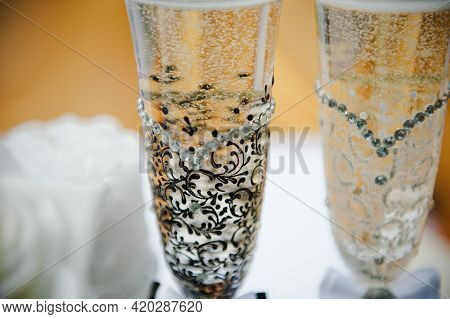 Close-up Bride And Groom Champagne Glasses. Wedding Glasses Of The Bride And Groom. Glass Decor