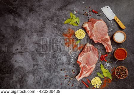 Raw Pork Chops With Spices And Cleaver On Dark Background. Top View.
