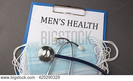 Folder With Paper Text En's Health , On A Table With A Stethoscope And Medical Masks, Medical