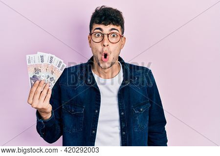 Young hispanic man holding icelandic krona banknotes scared and amazed with open mouth for surprise, disbelief face