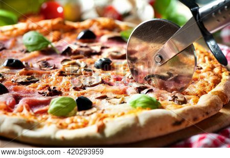 Pizza cutter (wheel) slicing pizza with tomato sauce, cheese, ham, olives, mushrooms and basil on wooden board
