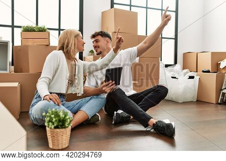 Young caucasian couple smiling happy using touchpad pointing with finger to the ceiling at new home.