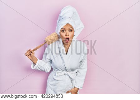 Young hispanic girl wearing bathrobe holding sponge scared and amazed with open mouth for surprise, disbelief face