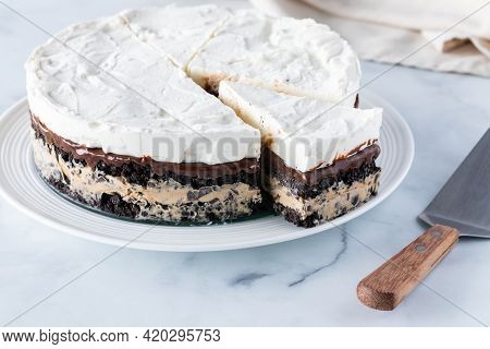 A Whole Frozen Layered Pie Including Mocha Ice Cream And Crushed Cookie Wafers, With One Slice Cut O