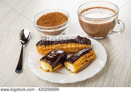 Teaspoon, Bowl Of Cocoa Powder With Sugar, Cup Of Cocoa With Milk, Whole Eclair With Chocolate Glaze