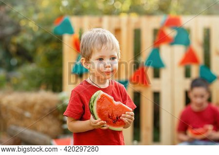 Portrait Of Beautiful Boy Holding Watermelon On Summer Day. Funny Kid Eating Watermelon Outdoors In
