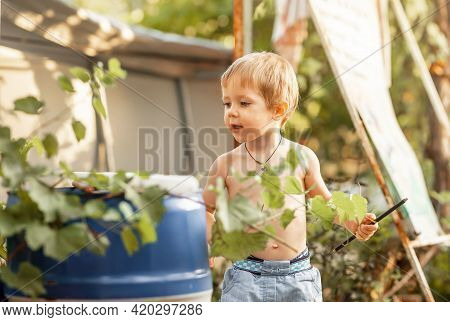 Happy Child Looking At The Camera. Sweet Happy Little Boy In The Park. Portrait Of Smiling Cute Litt