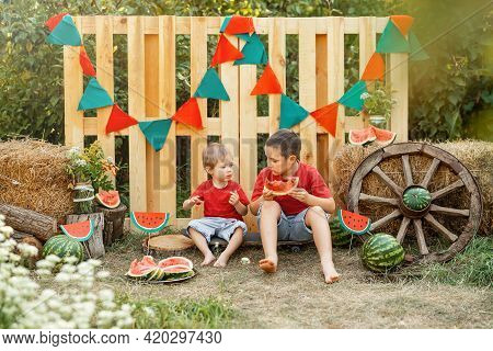 Funny Kids Eating Watermelon Outdoors In The Garden. Children Having Picnic Outdoors In Summer Park.