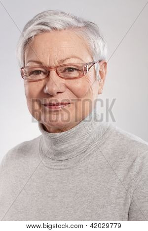 Portrait of smiling mature woman in polo-neck sweater and glasses.