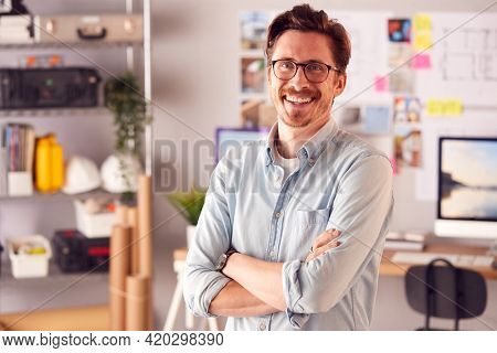 Portrait Of Smiling Male Architect In Office Standing By Desk