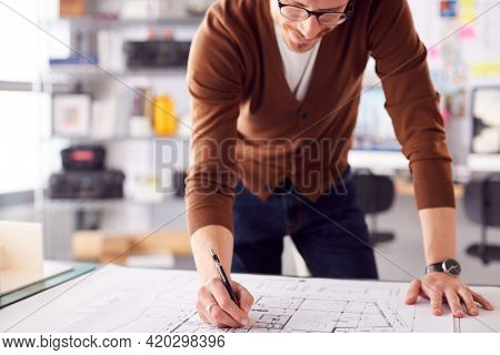 Male Architect Standing At Desk In Office Amending Building Plans