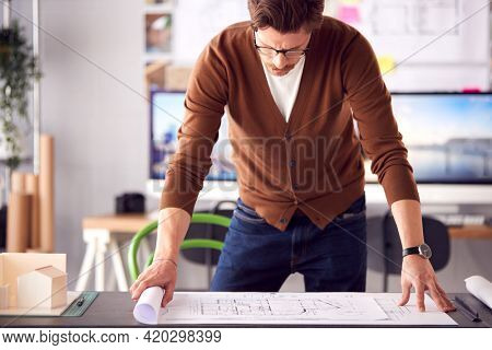 Male Architect In Office Unrolling Building Plan Or Blueprint On Desk