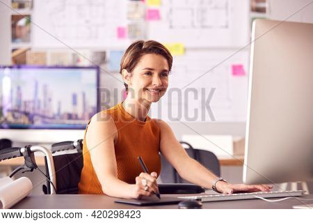 Female Architect In Office Working On Desktop Computer Using Graphics Tablet