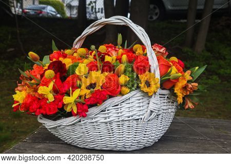 Beautiful basket with colorful flowers outdoor on table