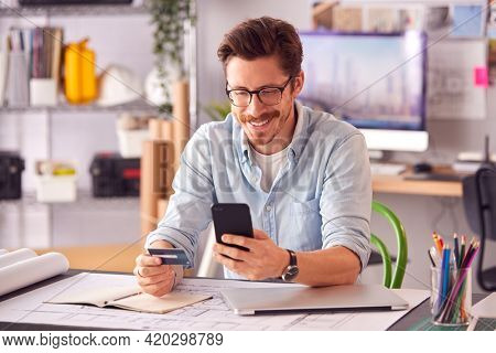 Male Architect In Office Working At Desk Making Online Purchase Using Credit Card On Mobile Phone