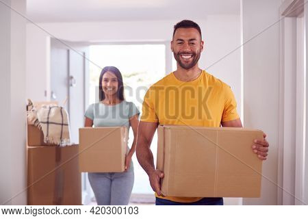 Portrait Of Couple Carrying Boxes Through Front Door Of New Home On Moving Day