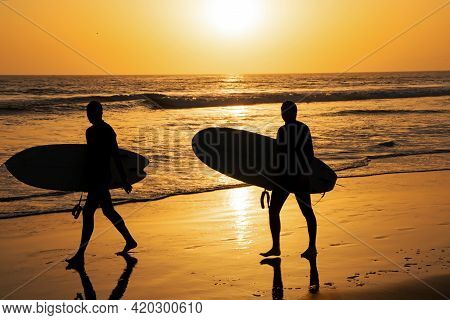 Tropical Beach Sea Ocean With Sunset Or Sunrise For Summer Travel Vacation. Silhouette Of Surfer Peo