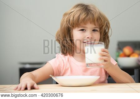 Cute Little Child With Glass Of Milk At Table In Kitchen. Kid Eating Breakfast. Child Eating Healthy