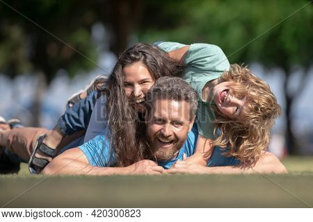Family Leisure Time. Portrait Of A Happy Family Hugging And Embracing In Park.