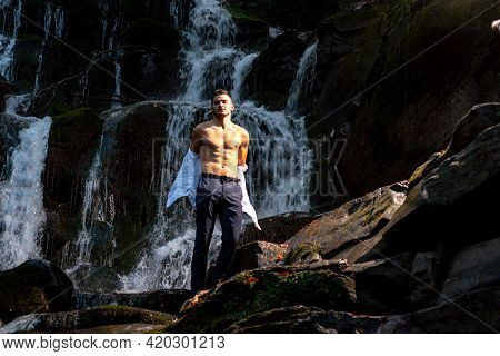 Muscular Man Going To Swim In Waterfall Water. Profit Business Concept. Businessman Undressing At Wa