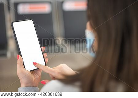 Mockup Image Of Female Hands Holding Black Mobile Phone With Blank White Screen Over Flight Board In