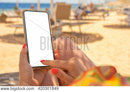 Closeup Of Young Woman's Hands Using White Mobile Smartphone Mockup On The Beach, Beach Resort And S