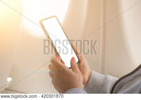 Woman Using Smartphone On Airplane. Closeup Image Of Woman Holding And Touching Mockup Cell Phone Ne