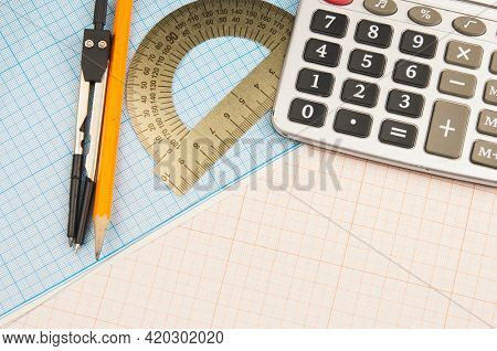 Mathematical instruments lie on a graph paper with copy space for text. Math graphic tools concept.